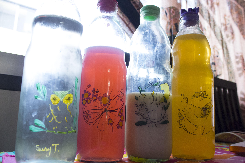 Botellas de la heladera, pintadas a mano por Susy T. Agua, Terma de frambuesa, leche descremada y jugo de mandarina.